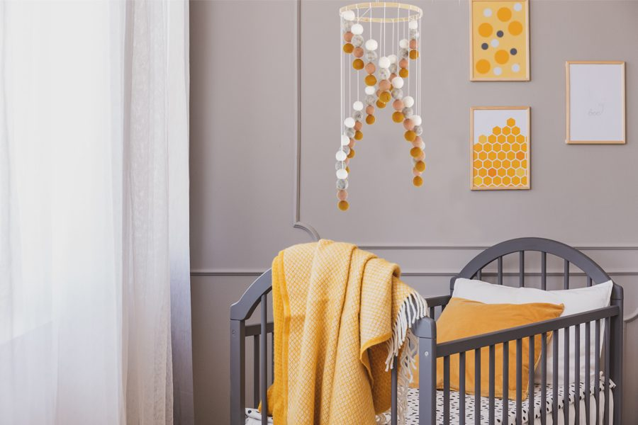 Yellow blanket on grey wooden crib in bright baby bedroom with yellow accents